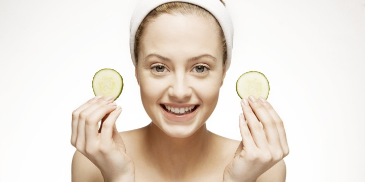 Smiling woman holding cucumber slices