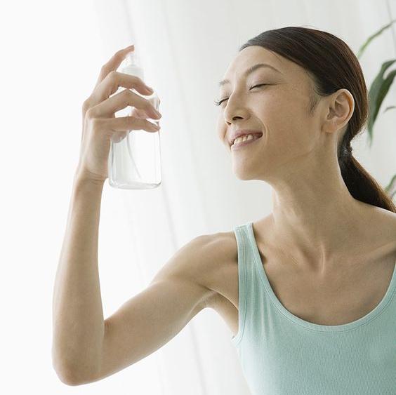 A woman spraying herself